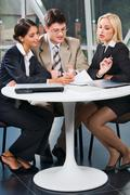 group of three young business people gathered together at a table discussing an - stock photo