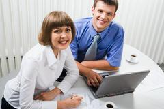 two young professionals gathered together around the laptop discussing important - stock photo