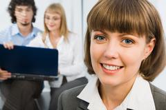Portrait of successful young business woman smiling on the background of busines Stock Photos