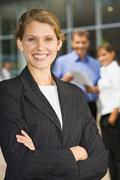portrait of successful smiling blond businesswoman in black suit with crossed ar - stock photo