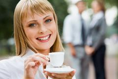 Beautiful young smiling woman with the cup of coffee outdoor Stock Photos