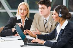 team of three young business people gathered together around the laptop discussi - stock photo