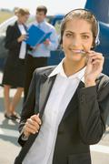 beautiful pilot with headset smiling on a background of two business people and - stock photo
