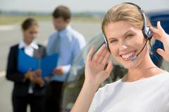 Beautiful customer representative with headset smiling on a background of two bu Stock Photos
