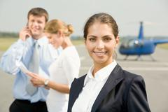 Portrait of confident young woman smiling on a background of two business people Stock Photos