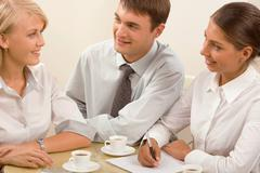 Stock Photo of group of young specialists gathered together discussing important project in the