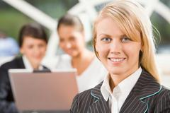 portrait of smiling blond caucasian woman and two talking businesspeople on the - stock photo