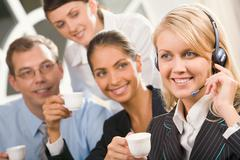 portrait of cute blond woman with headset and her three colleagues behind gazing - stock photo