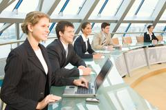 businesspeople sitting at the round table in large light conference hall with gl - stock photo