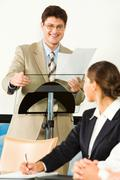 Portrait of smiling businessman holding documents and touching rostrum looking a Stock Photos