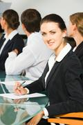 Stock Photo of confident young woman on the background of three business people
