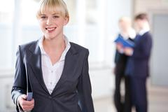 Portrait of young business woman holding a folder on the background of people Stock Photos