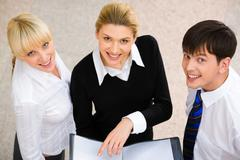Image of three smiling business people looking at camera Stock Photos