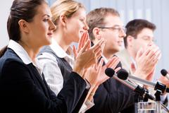portrait of several confident people clapping their hands - stock photo