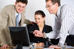 portrait of three business people looking at monitor of laptop - stock photo
