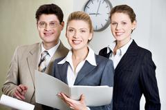 Portrait of three smiling businesspeople looking at camera Stock Photos