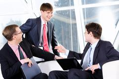 three business men are discussing a terms of transaction - stock photo