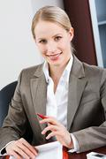 portrait of bossy woman sitting at a table and looking at camera - stock photo