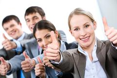 portrait of business people giving the thumbs-up sign - stock photo