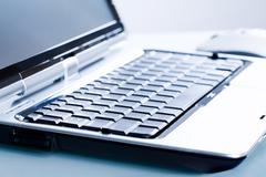 close-up of opened personal computer on a workplace - stock photo