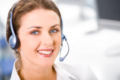face of young smiling confident woman with headset - stock photo