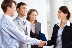 Business people are shaking hands confirming a sale Stock Photos
