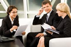 portrait of three white collar workers discussing a new idea - stock photo