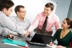 Stock Photo of portrait of confident people shaking hands at business meeting