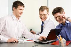 team of three happy men discussing their business project - stock photo