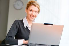 Portrait of pretty woman typing on the laptop in the office Stock Photos