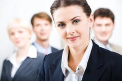 photo of leader with her business team in the office - stock photo