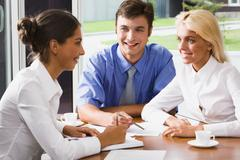 Three business persons are discussing ideas in the office Stock Photos