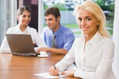 pretty smiling woman on a background of her the coworkers in the office - stock photo