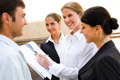 Team of young smiling professionals are discussing  new business ideas backgroun Stock Photos