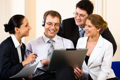 team of four young business people gathered together around the laptop communica - stock photo