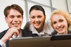 Portrait of three smiling business people looking at the laptop Stock Photos