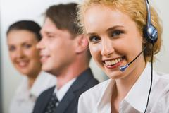a friendly smiling customer support operator on a background of two business peo - stock photo