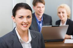 young beautiful smiling woman in a working environment on a background of her bu - stock photo