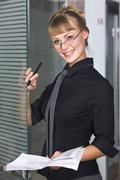 Svelte young woman in black business blouse is holding business plan in her hand Stock Photos