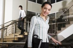 Pretty young business holding document case in her hand going downstairs and bus Stock Photos