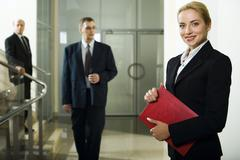 Smart beautiful businesswoman with red case in her hands and two men behind her Stock Photos