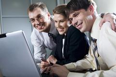 Three smiling businessmen looking at the laptop Stock Photos