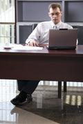 smart businessman seating comfortably at the table working on his lap top at the - stock photo