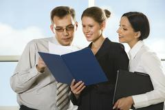 smiling young woman showing documents to her boss and curious girl looking into - stock photo