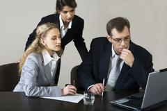 worried young businessman sitting at the table and two businesswomen behind him - stock photo