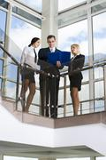 Businessman showing documents to his colleagues on stairs in the building with g Stock Photos