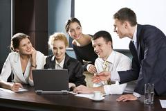 Large group of young businessman gathered together around the laptop discussing Stock Photos