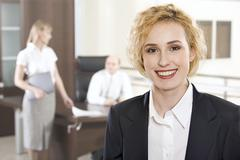 portrait of pretty smiling businesswoman in the office and two businesspeople on - stock photo