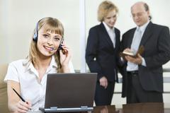 portrait of beautiful smiling blond woman in gray suit touching headset on her h - stock photo