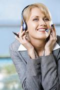 portrait of beautiful smiling blond businesswoman in gray suit touching headset - stock photo